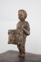 A ceramic sculpture by Michael Hermesh that depicts two children facing each other, one carries a drum and the other is wearing a bird mask