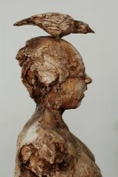 A mobile mixed media sculpture by Michael Hermesh that depicts an armless couple each with a bird on their head