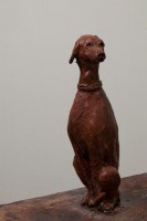 A ceramic sculpture by Michael Hermesh that depicts a man flying a balloon with a dog at his side