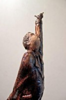 A ceramic sculpture by Michael Hermesh depicting a man in a raincoat reaching for the sky balancing precariously