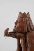 A ceramic sculpture by Michael Hermesh depicting a barefoot King examining a mouse