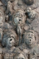 A ceramic relief by Michael Hermesh that depicts a choir singing in monk's robes and mouse ears