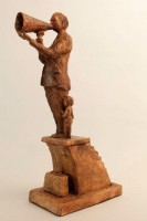 A ceramic sculpture by Michael Hermesh that depicts a man with a megaphone standing at the the top of a set of stairs