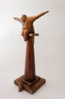 A Ceramic sculpture by Michael Hermesh that depicts a man sitting on a pillar with his arms spread out as if to fly while a dog looks upward at him