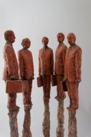 A mixed media mobile sculpture by Michael Hermesh that depicts five men in suits atop shrouded bodies and a grieving woman in the center
